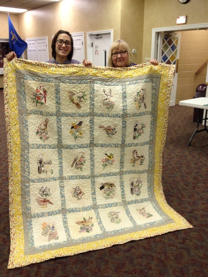 Ramona Clark and Cleo Lampos with finished quilt started by Cleo's mother in the Dust Bowl with feed sack muslin squares and transfers from newspapers.