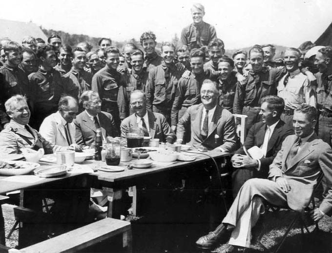 President Franklin Roosevelt visited with CCC enrollees near Camp Roosevelt on August 12, 1933, at Big Meadows, Skyland Drive, Virginia. Seated from left are Maj. Gen. Paul B. Malone, Louis M. Howe, Harold L. Ickes, Robert Fechner, FDR, Henry A. Wallace, and Rexford Tugwell. (35-GE-3A-5)